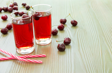 Two glasses of cherry juice, straws and empty space. Left two glasses of cherry juice around scattered cherries, right empty space for text on light green background. Horizontal. Close. Daylight.