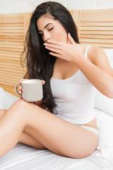 Cute young beautiful woman drinking coffee and yawning