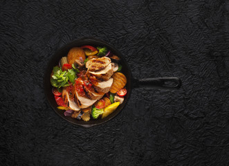 roast beef in a iron pan with vegetables, top view