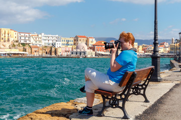 The woman with the camera on the waterfront of Chania.