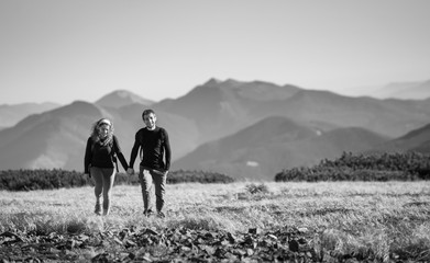 Young happy couple hiking in the beautiful mountains on warm sunny day. Man and woman smiling and holding hands. black and white