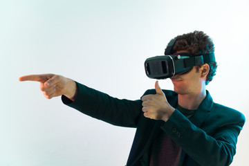 Young man points something with his finger in a virtual reality world . Shot on Canon 5D Mark II