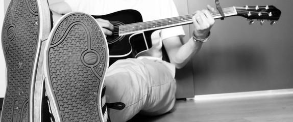 Junger Mann spielt Gitarre, sitzend am Boden, schwarz weiß
