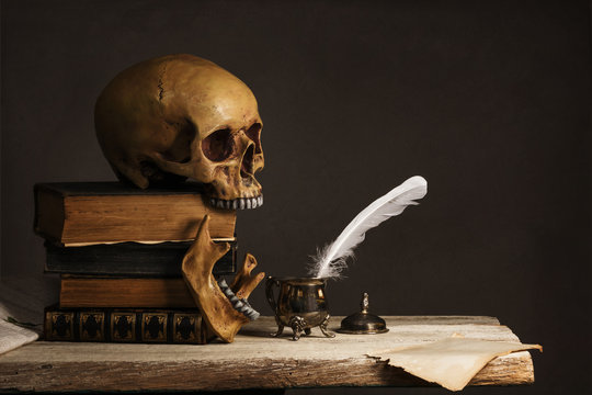 human Skull on old Books with empty Page, Feather and Inkpot