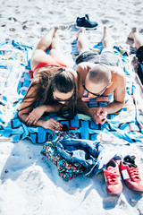 Couple of friends man and women at the beach in summertime tanning leaning on their towel, using smart phone - summer, social network, technology concept