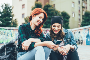 Two young handsome caucasian blonde and redhead straight hair women sitting on a staircase using smart phone, looking downward the screen - social network, technology, communication concept