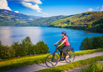woman with e-bike cycling beside a beautiful lake-lake and bike