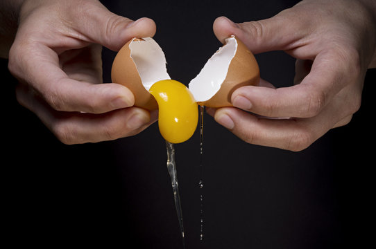 female hands breaking a raw egg