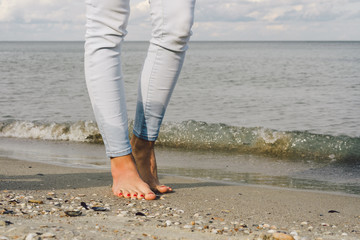 Female feet in jeans barefoot walk on the sea water on the beach