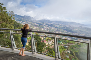 Woman looking at Madeira landscape from Cabo Girao famous viewpoint