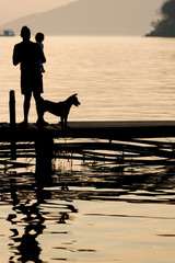 Man holding a child on wooden Pier during sunset with pet, Famil