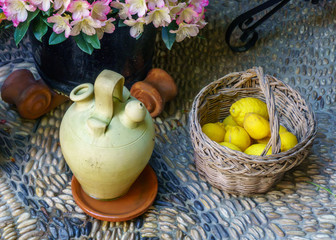 Craft pitcher and basquet with lemons on a cobbled floor