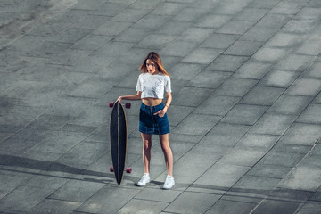 Beautiful stylish woman standing with longboard in the city urban landscape. Fashionable girl in jeans skirt on a background of concrete tiles.