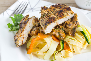Roasted chicken with pasta and colorful vegetables