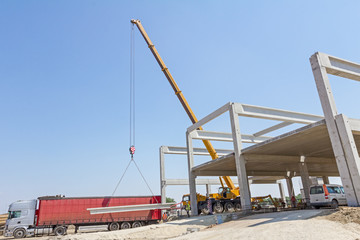 Mobile crane is unloading concrete joist from truck trailer.