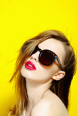 Portrait of a beautiful girl in glasses on a yellow background in the studio