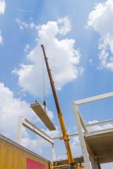 Mobile crane is unloading concrete joist from truck trailer.