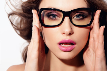 Fashion studio portrait of pretty young hipster brunette woman with bright sexy make up and glasses