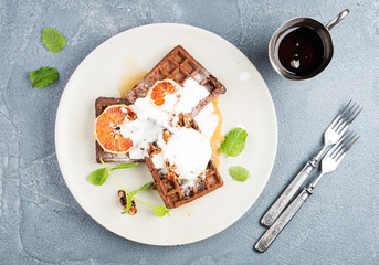 Belgian soft waffles with blood orange, cream, marple syrup and mint  on white plates