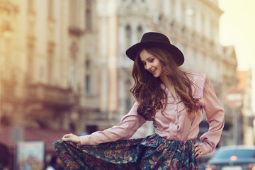 Outdoor portrait of young beautiful happy lady posing on street. Model wearing stylish clothes. Girl looking down. Sunny day. Female fashion. City lifestyle. Copy space. Toned style instagram filters