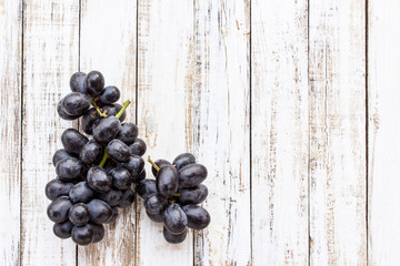 Grapes on white wooden table background