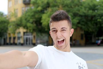 Handsome man making selfie and grimacing in urban street