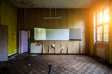 Abandoned classroom with the words on the chalkboard and old wallpaper