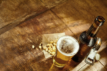 Glass of Beer on Table with Opener and Peanuts