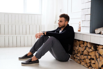 A man in black jacket resting near fireplace.
