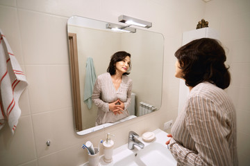 Beauty and health concept. Picture of attractive brunette Asian senior woman wearing pajamas, looking and smiling at herself in the mirror while doing night routine procedures before going to bed