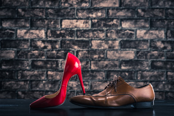 赤いハイヒールに踏まれている革靴