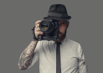 A man with dslr isolated on grey background.