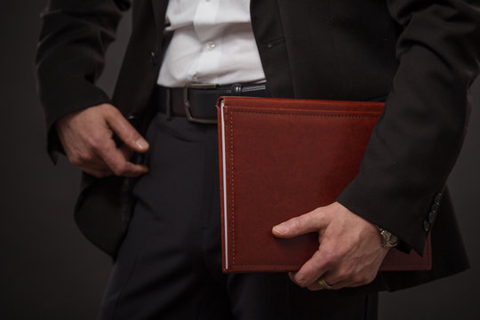 Low view of businessman holding dark red register with security information. Young man going to report at business meeting.
