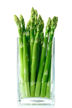 asparagus standing in a glass vase with water on white isolated background