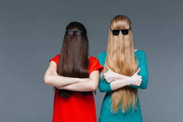 Two funny women covered face with long hair