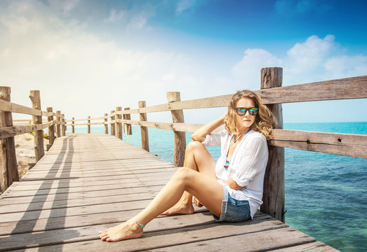 attractive young woman with curly hair  sits on a wooden bridge