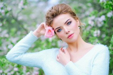 Beautiful woman portrait in holding delicate pink rose
