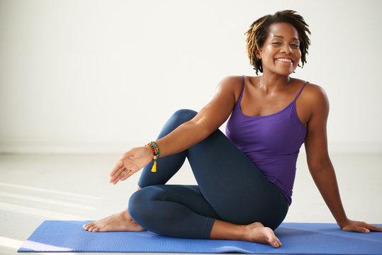 Cheerful African-American woman practicing asana in yoga class
