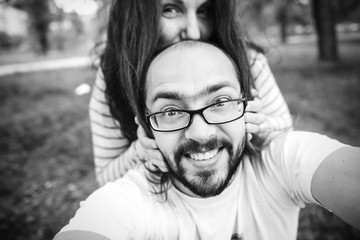 ? Handsome man with beard and young pretty cheerful girl with glasses making selfie.