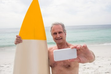 Senior man with surfboard taking a selfie on mobile phone