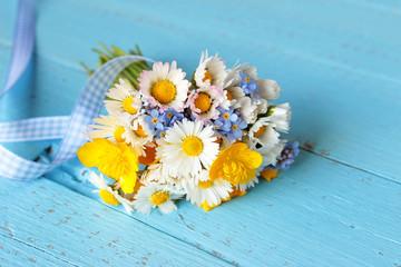 Blumenstrauß mit selbst gepflückten Blumen, Gänseblümchen, Sumpfdotterblume, Vergissmeinnicht  auf blauem Holz