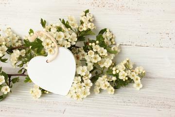 Weißdornzweige mit weißem Herz auf weißem Holz