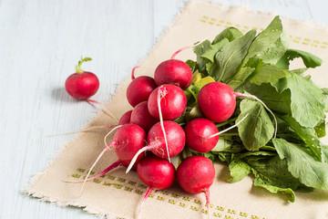 Fresh radishes.  Young fresh radishes on a napkin on a light wooden background.