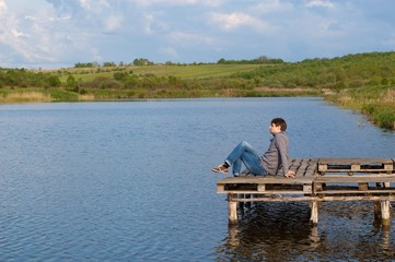 Man sitting on the pier of a lake
