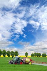 Konventionelle Landwirtschaft: Traktor mit Feldspitze sprüht Pflanzenschutzmittel auf Feld mit Getreide