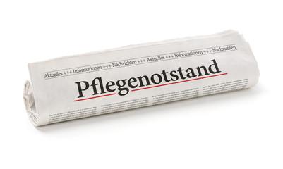 Zeitungsrolle mit der Überschrift Pflegenotstand