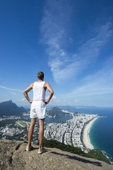 Athlete in vintage white uniform stands with hands on hips at an overlook view of the Rio de Janeiro Brazil skyline