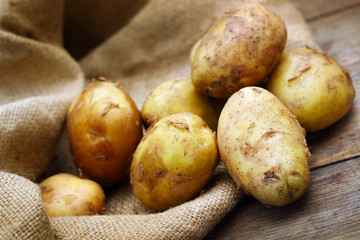 Raw potatoes on burlap background