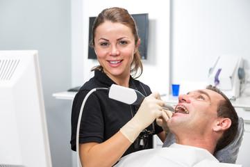 Dentist scanning patient's teeth with CEREC scanner
