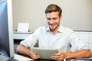 Smiling businessman using digital tablet in office